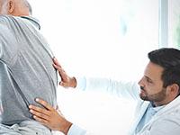 Un médecin ausculte un patient souffrant d'une sciatique
